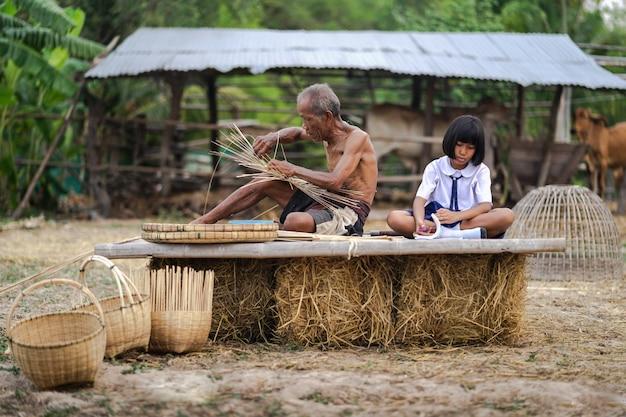Hombre mayor y artesanía de bambú con chica estudiante, estilo de vida de los locales, tailandia