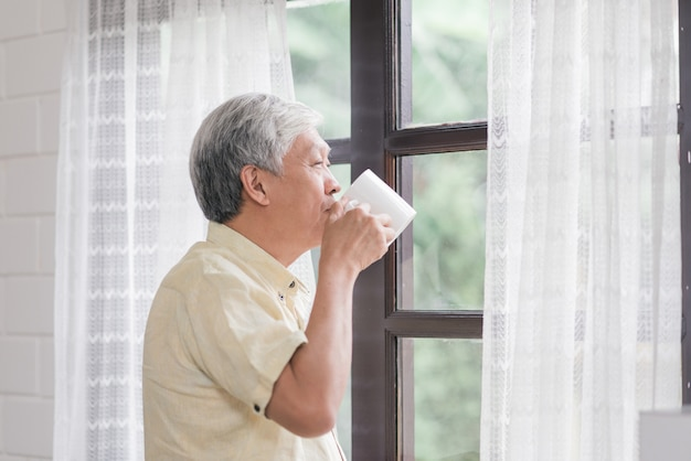El hombre mayor asiático feliz que sonríe y que bebe una taza de café o de té cerca de la ventana en la sala de estar, el varón mayor de asia abre las cortinas y se relaja por la mañana.
