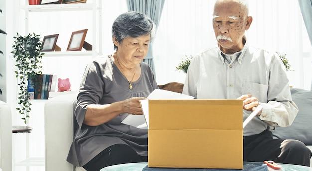 El hombre mayor asiático y la mujer abren la caja con la cara de la sonrisa.
