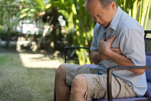 Hombre mayor asiático sintiendo dolor que sufre de un ataque al corazón.