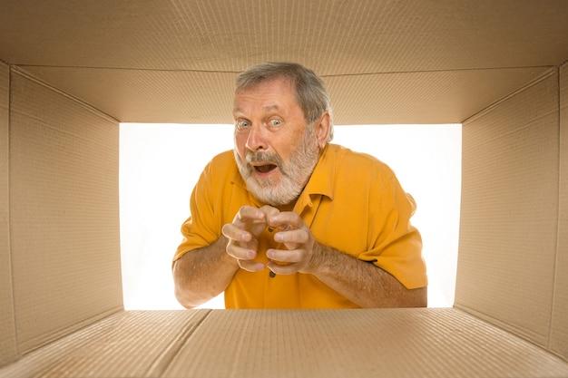 Hombre mayor asombrado abriendo el paquete postal más grande