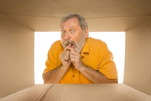 Hombre mayor asombrado que abre el paquete postal más grande aislado en blanco. modelo masculino feliz en la parte superior de la caja de cartón