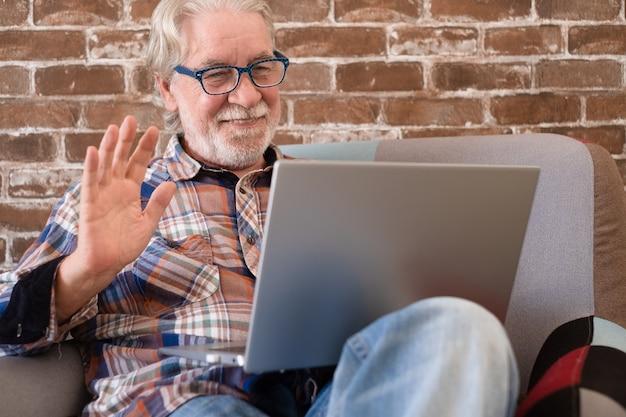 Hombre mayor atractivo sonriente sentado en su casa en un sillón con ordenador portátil para videollamadas