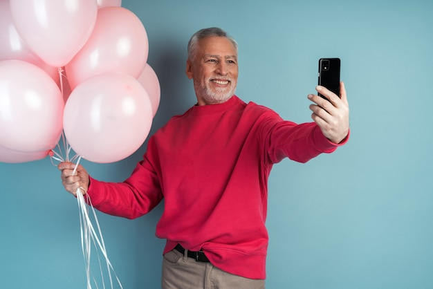 Hombre mayor atractivo sostiene globos y toma un selfie en un teléfono celular