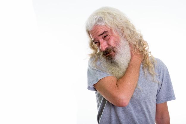 Hombre mayor con barba que tiene dolor en el cuello