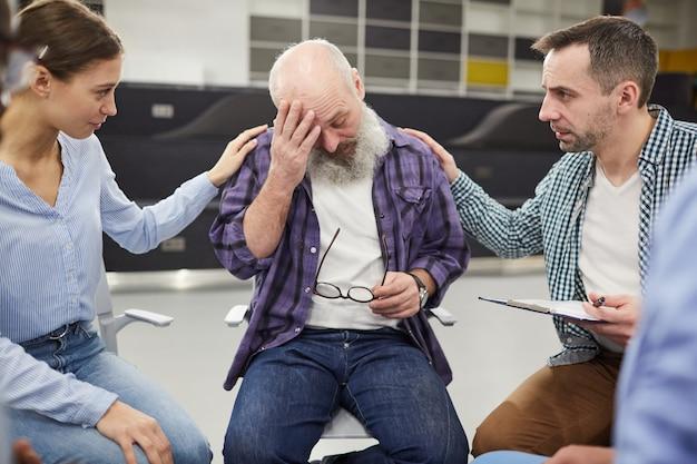 Hombre mayor barbudo llorando en grupo de apoyo