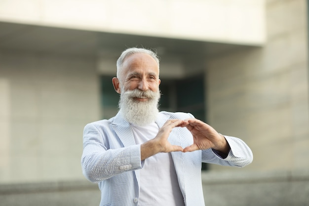 Hombre mayor barbudo muestra signo de amor al aire libre