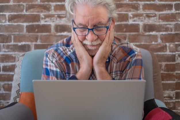 Hombre mayor barbudo sentado en su casa en un sillón con ordenador portátil. pared de ladrillo en segundo plano.
