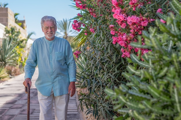 Hombre mayor caminando al aire libre con la ayuda de un palo de madera. jardín en flor