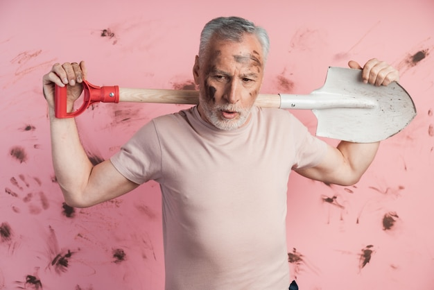 Hombre mayor cansado con la cara sucia sosteniendo una pala sobre sus hombros