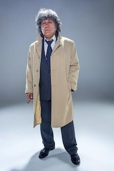 El hombre mayor en capa con cigarro como detective o jefe de la mafia.