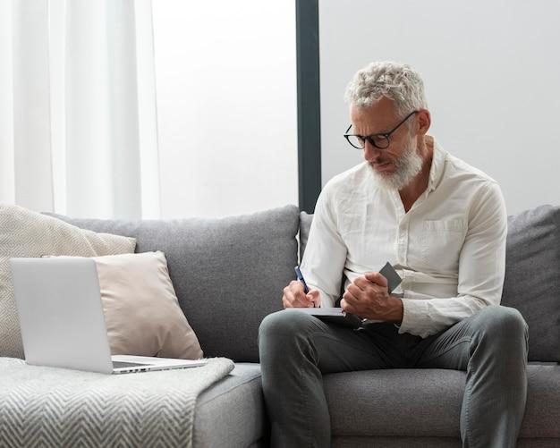 Hombre mayor en casa estudiando en el portátil y tomando notas