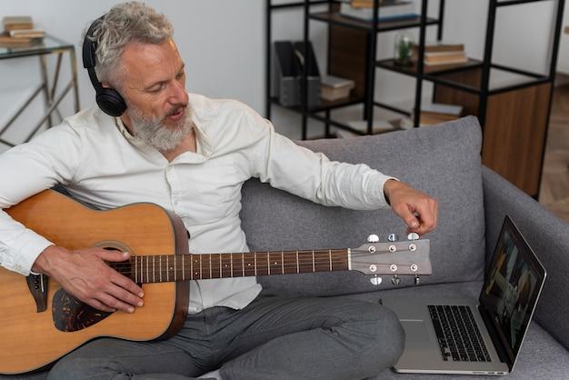 Hombre mayor en casa en el sofá usando la computadora portátil para estudiar lecciones de guitarra