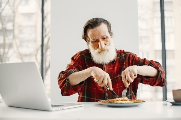 Hombre mayor casual comiendo. ordenador portátil sobre la mesa. deliciosa comida sana.