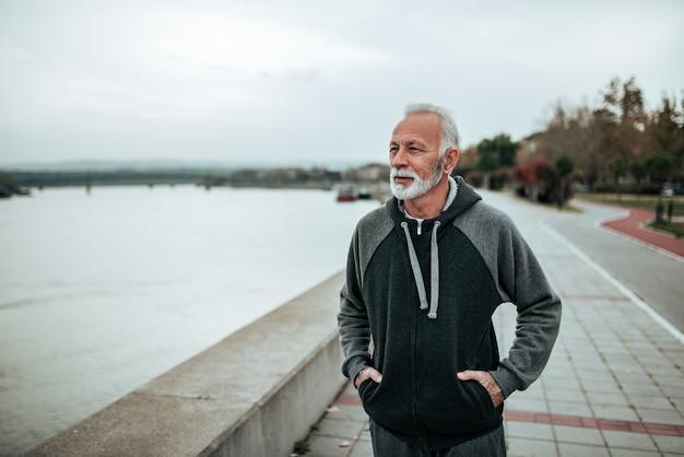 Hombre mayor casual que camina por el río en la ciudad.