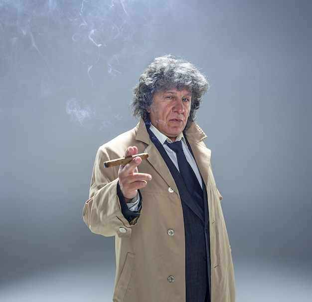 El hombre mayor con cigarro como detective o jefe de la mafia en gris