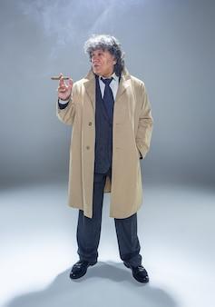 El hombre mayor con cigarro como detective o jefe de la mafia