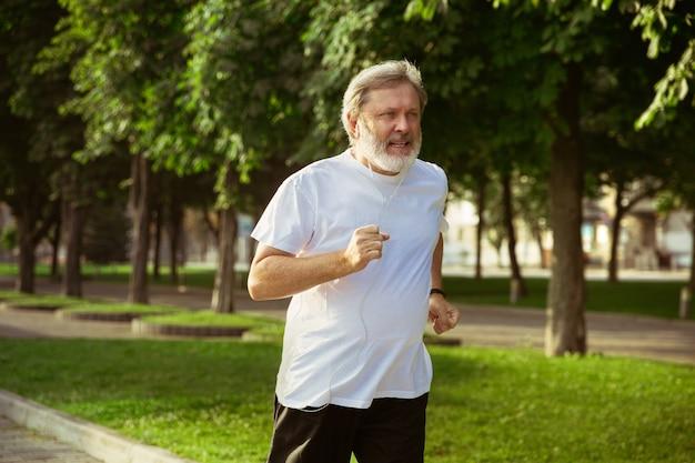 Hombre mayor como corredor con brazalete o rastreador de fitness en la calle de la ciudad. modelo masculino caucásico que practica jogging y entrenamientos de cardio en la mañana de verano. estilo de vida saludable, deporte, concepto de actividad.