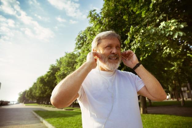Hombre mayor como corredor con rastreador de fitness en la calle de la ciudad. modelo masculino caucásico usando gadgets mientras hace jogging y entrenamiento cardiovascular en la mañana de verano. estilo de vida saludable, deporte, concepto de actividad.