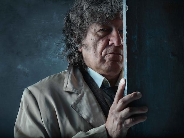 El hombre mayor como detective o jefe de la mafia en gris