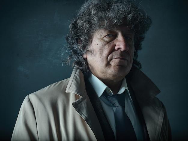 El hombre mayor como detective o jefe de la mafia sobre fondo gris de estudio