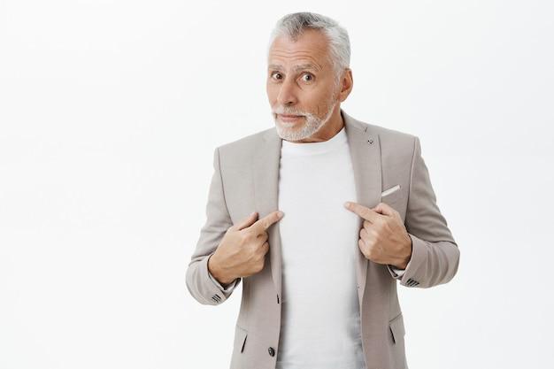 Hombre mayor confundido y sorprendido apuntando a sí mismo desconcertado