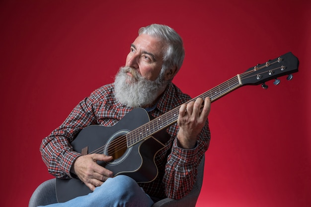 Hombre mayor contemplado que toca la guitarra contra fondo rojo