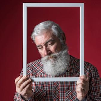 Hombre mayor deprimido que lleva a cabo el marco blanco de la frontera delante de su cara contra fondo coloreado