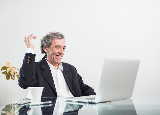Hombre mayor emocionado sonriente que se sienta en el lugar de trabajo que mira el ordenador portátil