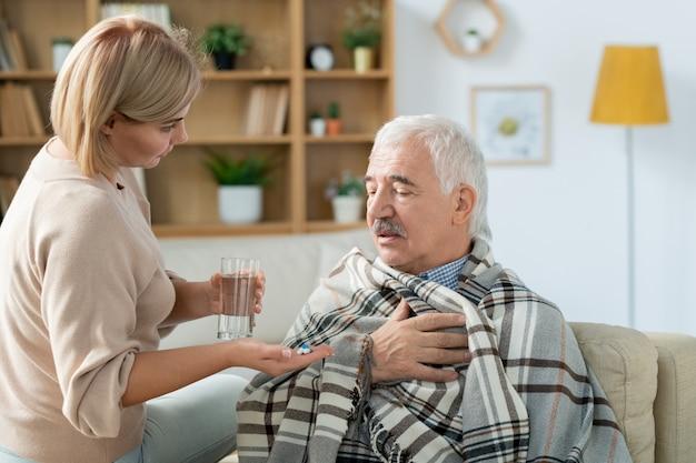 Hombre mayor enfermo envuelto en cuadros sentado en el sofá frente a su cuidadosa hija llevándole un vaso de agua y pastillas