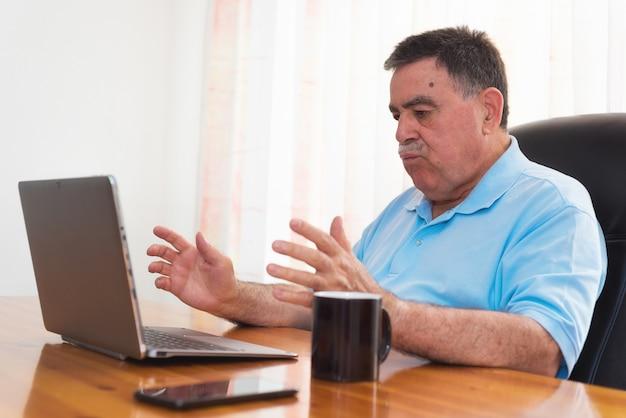 Hombre mayor enojado que trabaja en la computadora portátil. emoción negativa