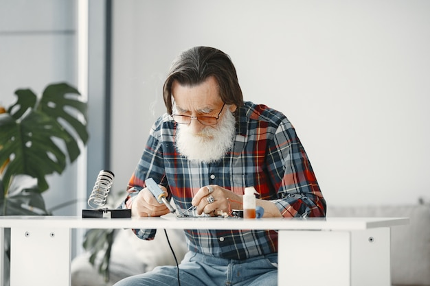 Hombre mayor con equipo para soldar. trabajando en casa.