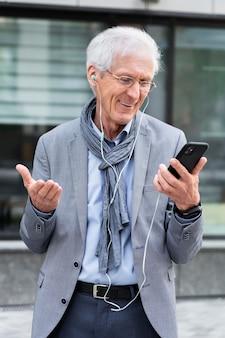 Hombre mayor con estilo en la ciudad con teléfono inteligente y auriculares para videollamada