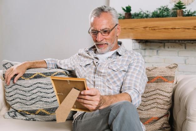 Hombre mayor feliz que se sienta en el sofá que mira el marco de la foto