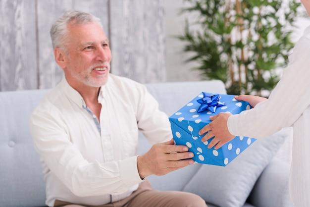 Hombre mayor feliz que se sienta en el sofá que recibe el frente del regalo un muchacho