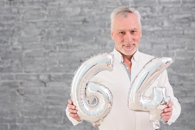Hombre mayor feliz que sostiene el globo de plata en su 64 cumpleaños