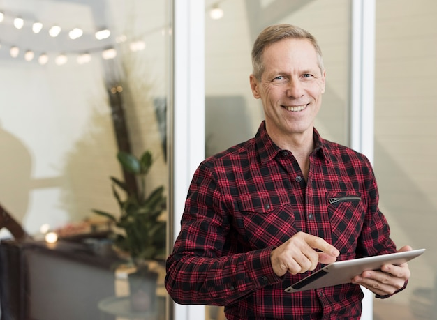 Hombre mayor guapo sosteniendo una tableta