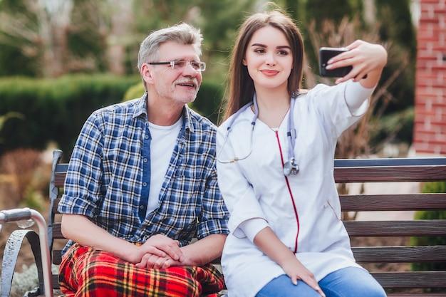 Hombre mayor hablando con él niños en el teléfono, cerca del jardín con la doctora