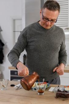 Hombre mayor hace café turco fresco en turco y desayuno saludable con verduras