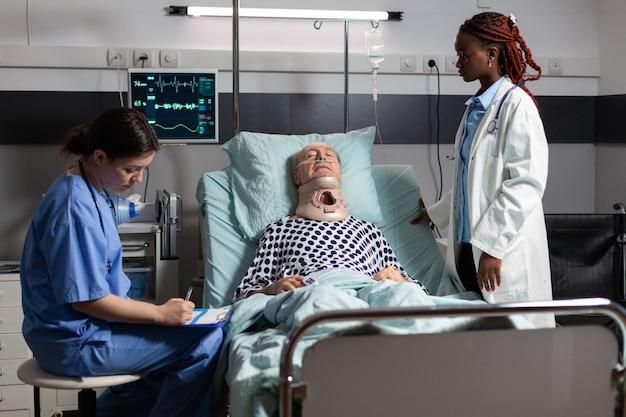 Hombre mayor herido con collarín tendido en la cama