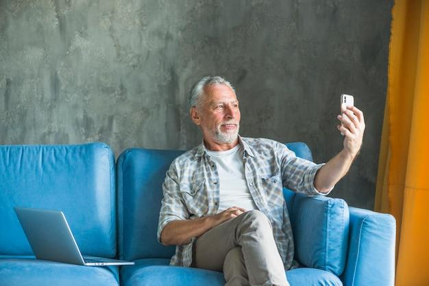 Hombre mayor jubilado tomando selfie a través del teléfono móvil