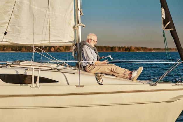 Hombre mayor leyendo un libro y relajándose mientras está sentado en el costado del velero o la cubierta del yate flotante