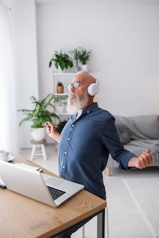 Hombre mayor, llevando, auriculares, plano medio