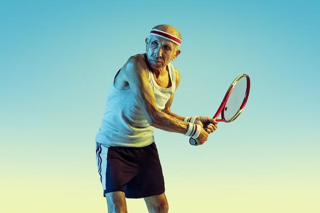 Hombre mayor, llevando, ropa deportiva, jugar al tenis, en, gradiente