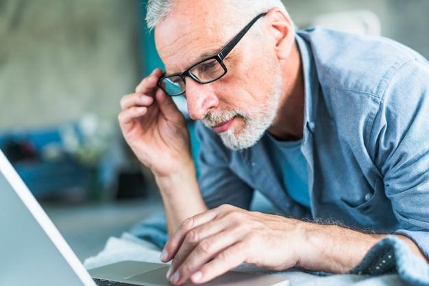 Hombre mayor con la mano en las lentes que miran la computadora portátil