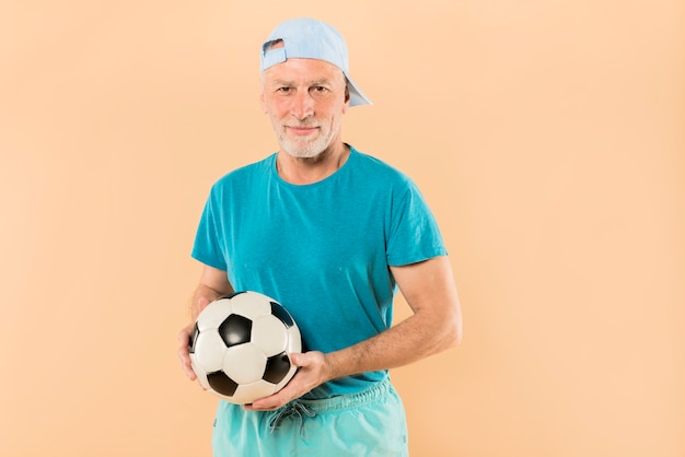 Hombre mayor moderno con pelota de fútbol