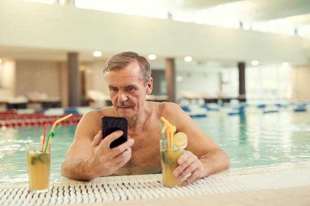 Hombre mayor moderno con smartphone en la piscina