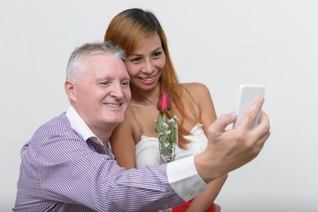 Hombre mayor y mujer asiática madura como pareja juntos y enamorados contra un blanco