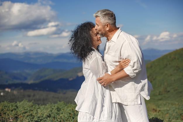 Hombre mayor y mujer en las montañas. pareja adulta enamorada al atardecer. hombre con camisa blanca.