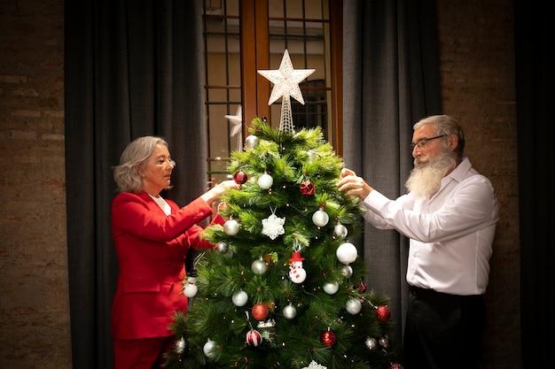 Hombre mayor y mujer que configuran el árbol de navidad